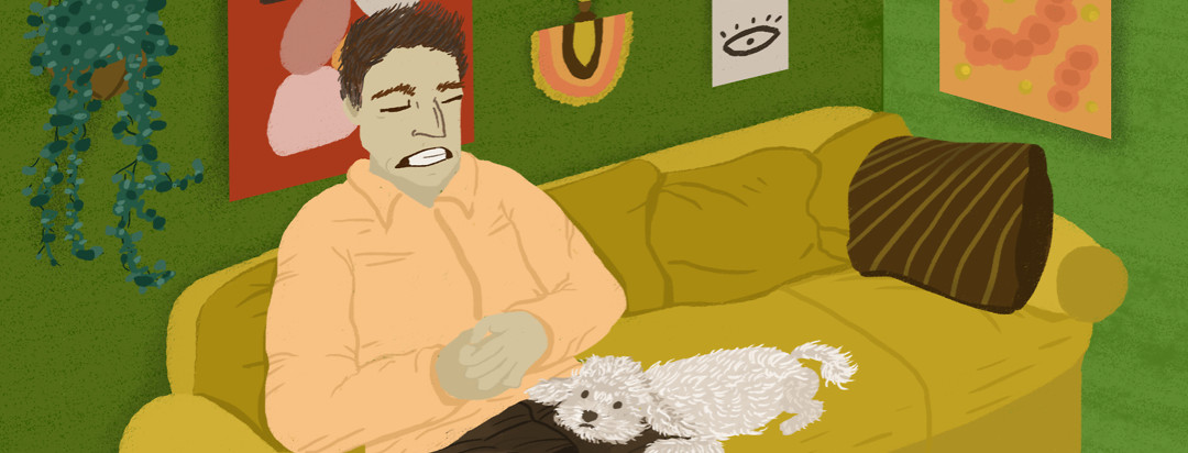 A man sitting on a living room couch clutches his stomach, experiencing intense abdominal pain, while his Bichon Frise rests his head on his owner's leg.