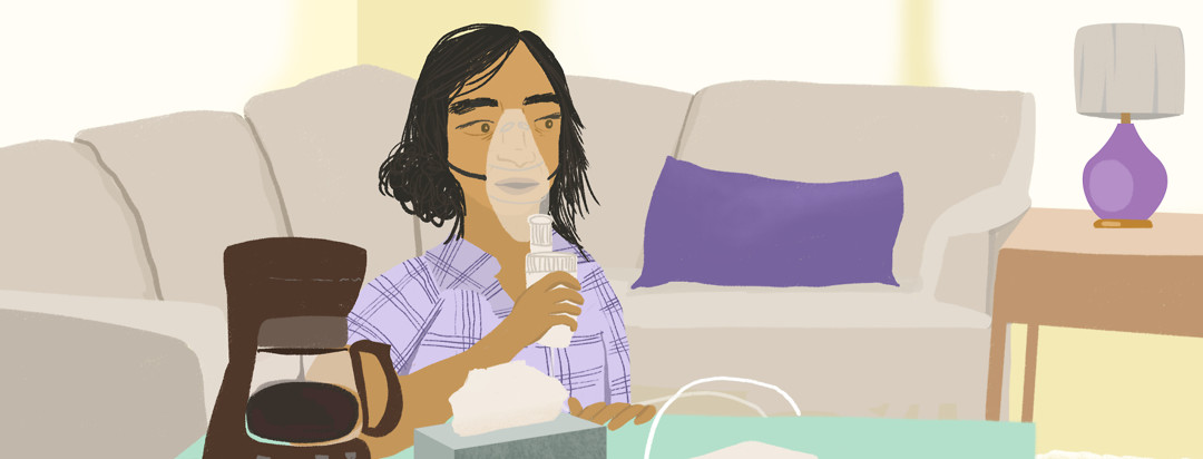 A person in pajamas does their cystic fibrosis treatments with a nebulizer while their morning coffee is brewing
