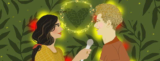 A woman interviews her husband under a wreath with a heart inside; leaf sprigs and flashing lights surround them.