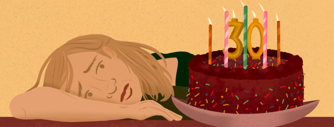 Person lays head on table looking worriedly at birthday cake with 30 candles