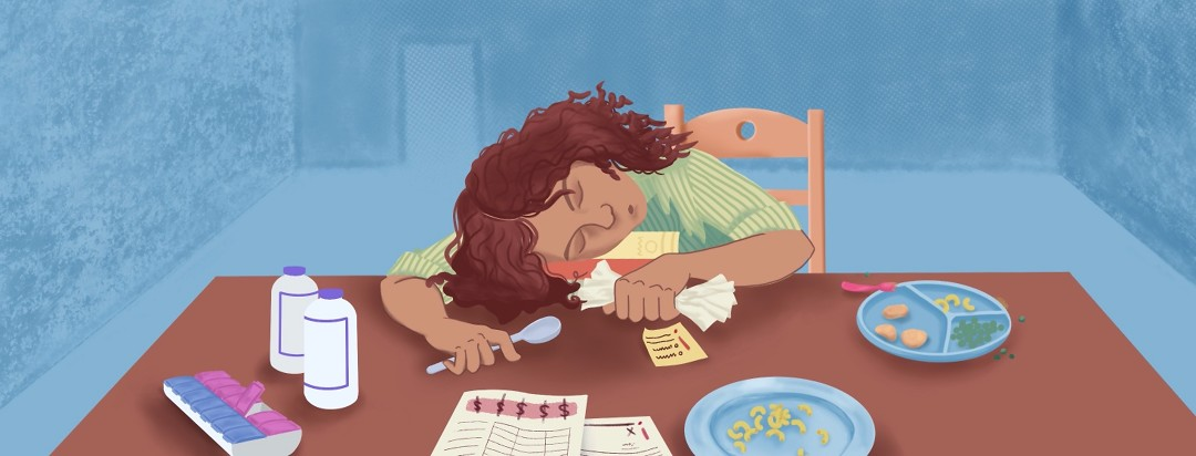 A woman asleep at a table stacked with paperwork, books, a pill sorter, and a half-eaten dinner for mom and child.