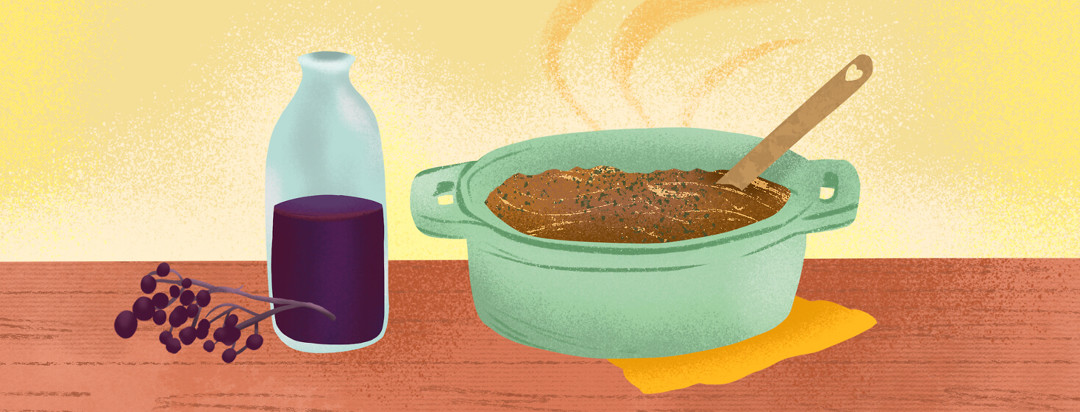 Elderberry syrup and Dutch oven filled with warm soup on wooden table