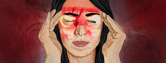 A women presses her temples with her fingers due to a migraine