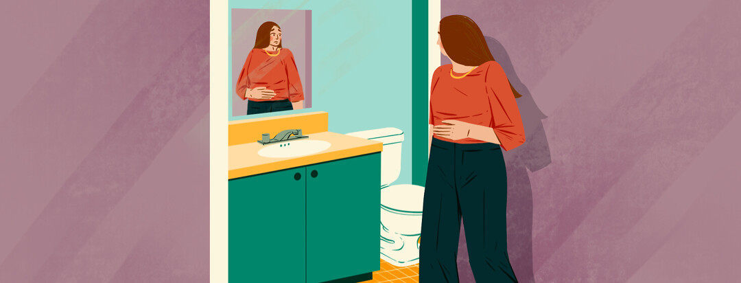 Woman entering bathroom clutches stomach and stares in mirror