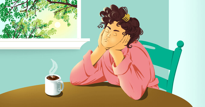 Tired woman sitting at a table with a mug of coffee.